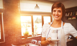 Composite image of smiling waitress holding a cup of coffee Royalty Free Stock Images