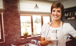 Composite image of smiling waitress holding a cup of coffee Royalty Free Stock Photography