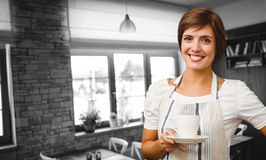 Composite image of smiling waitress holding a cup of coffee Stock Photography