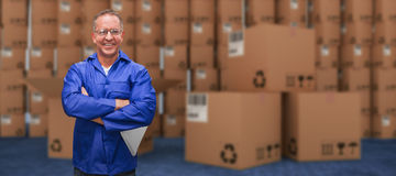 Composite image of smiling warehouse manager standing with arms crossed Stock Image