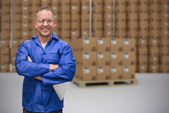Composite image of smiling warehouse manager standing with arms crossed Stock Photography