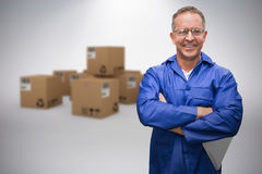 Composite image of smiling warehouse manager standing with arms crossed. Smiling warehouse manager standing with arms crossed against grey background Royalty Free Stock Image