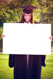 Composite image of a smiling woman as she holds and looks at a blank sheet in front of her Royalty Free Stock Photos