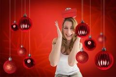 Composite image of smiling woman balancing christmas gift on her head Stock Photo