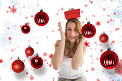 Composite image of smiling woman balancing christmas gift on her head Stock Images