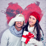 Composite image of smiling woman covering partners eyes and holding gift Royalty Free Stock Photography