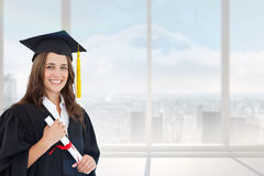 Composite image of a smiling woman with a degree in hand as she looks at the camera Royalty Free Stock Photo