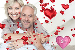 Composite image of smiling woman embracing mature man from behind on sofa. Smiling women embracing mature men from behind on sofa against love heart royalty free stock image