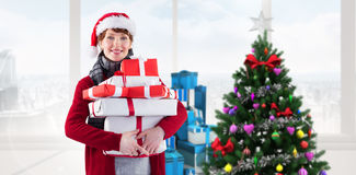 Composite image of smiling woman holding christmas presents Stock Photo