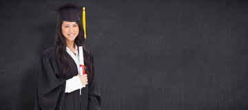 Composite image of a smiling woman holding her degree as she has graduated from university Stock Photo