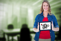 Composite image of smiling woman holding tablet pc Stock Photo