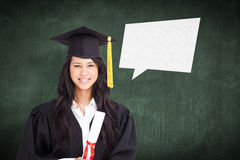 Composite image of a smiling woman looking at the camera while dressed in her graduation gown Stock Photo