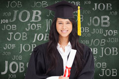 Composite image of a smiling woman looking at the camera while dressed in her graduation gown Royalty Free Stock Image