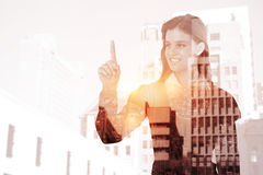 Composite image of smiling woman pointing something with her finger. Smiling woman pointing something with her finger against low angle view of city buildings Royalty Free Stock Photography