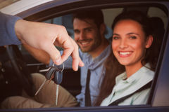 Composite image of smiling woman receiving keys from somebody. Smiling women receiving keys from somebody against portrait of young couple on road trip Royalty Free Stock Images