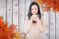 Composite image of smiling woman smelling hot beverage Stock Photo