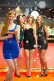 Composite image of smiling woman standing in front of her friends holding cocktail Royalty Free Stock Images