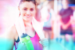 Composite image of smiling woman with towel and bottle. Abstract background against portrait of smiling woman with towel and bottle Royalty Free Stock Image