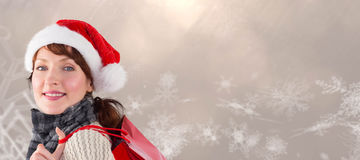 Composite image of smiling woman wearing santa hat Royalty Free Stock Photos