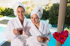 Composite image of smiling women in bathrobes having tea Royalty Free Stock Image