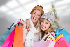 Composite image of smiling women looking at camera with shopping bags stock image