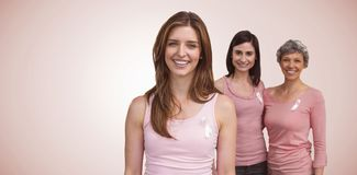 Composite image of smiling women in pink outfits posing for breast cancer awareness stock images