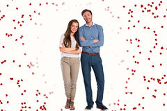Composite image of smiling young couple with arms crossed. Smiling young couple with arms crossed against red love hearts royalty free stock photo