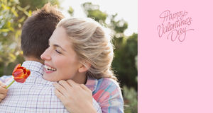 Composite image of smiling young couple embracing in park Royalty Free Stock Photo