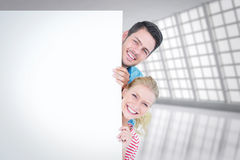 Composite image of smiling young couple hiding behind a blank sign Stock Images