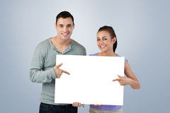 Composite image of smiling young couple pointing at sign they are holding Royalty Free Stock Image