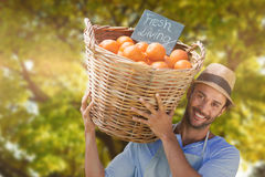 Composite image of smiling young man carrying orange fruits in wicker basket Stock Image