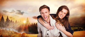 Composite image of smiling young man carrying woman Royalty Free Stock Photo