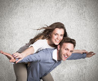 Composite image of smiling young man carrying woman Royalty Free Stock Images