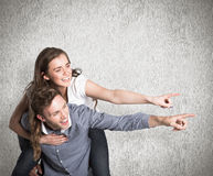 Composite image of smiling young man carrying woman Stock Photography