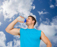 Composite image of smiling young man drinking water Royalty Free Stock Photography