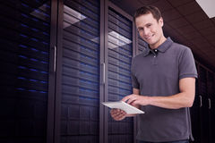 Composite image of smiling young man with tablet computer Royalty Free Stock Images