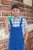 Composite image of smiling young repairman holding green card Royalty Free Stock Image