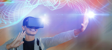 Composite image of smiling young woman gesturing while wearing virtual reality glasses stock photos