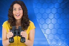 Composite image of smiling young woman holding binoculars Royalty Free Stock Images