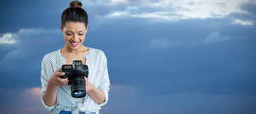 Composite image of smiling young woman holding digital camera. Smiling young woman holding digital camera against scenic view of seascape against cloudy sky stock image
