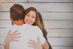 Composite image of smiling young woman hugging man Royalty Free Stock Photos