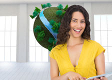 Composite image of smiling young woman scrolling on her tablet computer Stock Images