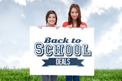 Composite image of smiling young women proudly holding a blank poster Stock Photo