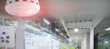 Composite image of smoke and fire detector. Smoke and fire detector against college hallway Stock Images