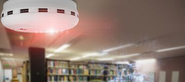 Composite image of smoke and fire detector. Smoke and fire detector against computer desks in the library Royalty Free Stock Photography