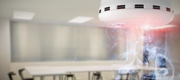 Composite image of smoke and fire detector. Smoke and fire detector against empty class room Royalty Free Stock Images