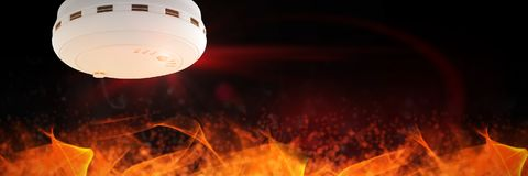 Composite image of smoke and fire detector. Smoke and fire detector against large flames on black background Royalty Free Stock Photo