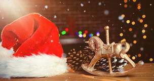 Composite image of snow falling. Snow falling against christmas decorations on table Stock Photography