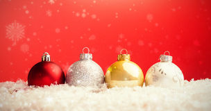 Composite image of snow falling. Snow falling against multi colored christmas bauble Royalty Free Stock Image
