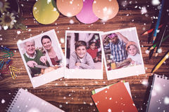Composite image of snow falling. Snow falling against overhead view of office supplies with blank instant photos royalty free stock image